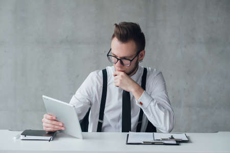 Professional career. Modern company. Head hunter focused on reading CV on tablet.
