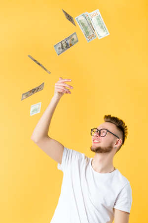 Easy income. Portrait of successful hipster guy. Young man in glasses throwing hundred dollar bills up in the air.