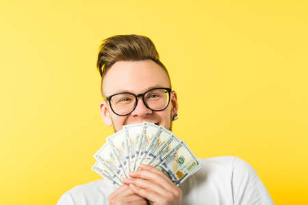 Happy young man bearded hipster holding dollar cash bunch covering mouth hiding behind money. Generous sum salary. 版權商用圖片