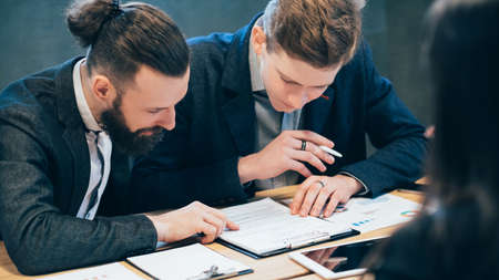Partnership and cooperation. Professional relationship. Corporate meeting. Young men reading business contract.