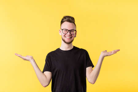 Portrait of cheerful millennial guy smiling, showing both hands open palms, comparing your options. Copy space.