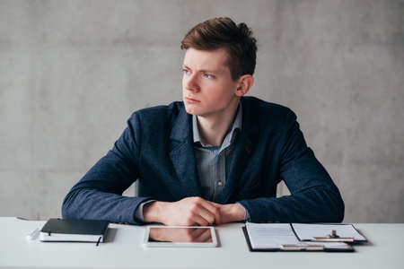 Office lifestyle. Portrait of young business man sitting at desk over gray wall background. Confident facial expression. Stock fotó