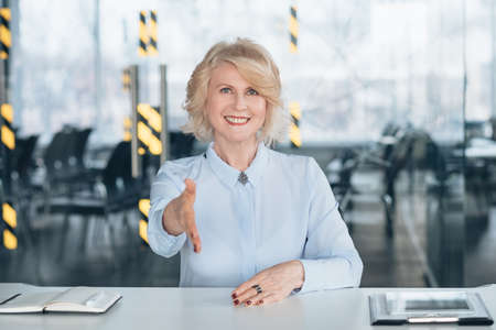 Friendly senior lady at work. Welcoming hand outstretched. Professional career growth at successful company corporate.