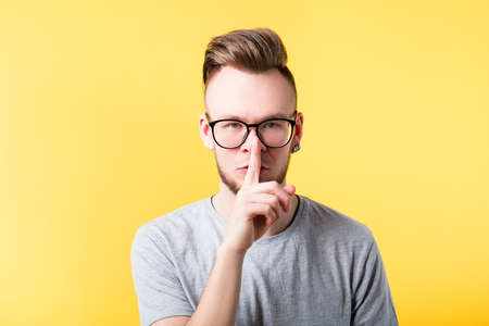 Shh be quiet secret silence gesture. Young man showing hush sign shushing finger on lips. Serious somber facial expression. Stockfoto