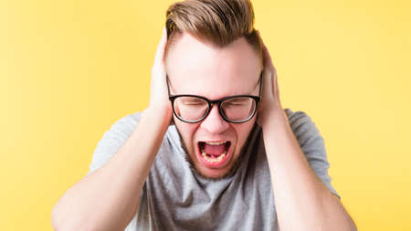 Stop talking. Portrait of frustrated hipster guy covering ears. Mad young emotional man screaming in pain. Copy space.