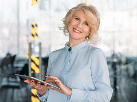 Smiling business lady with tablet. Digital analysis. Great sales financial company performance. Competent management.