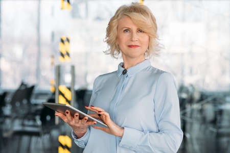 Company executive at work. Confident senior lady studying tablet report data. Smart corporate ceo. Business intelligence.
