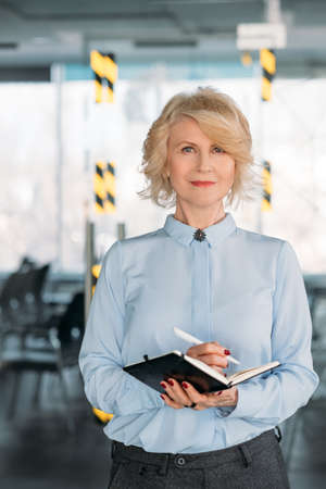 Senior business female portrait. Confident corporate expert making notes in day planner. Objectives ideas achievements.