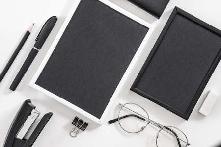 Business life essentials. Office supplies set. Flat lay of blank photo frames, eyeglasses, stationery. Mockup. 写真素材