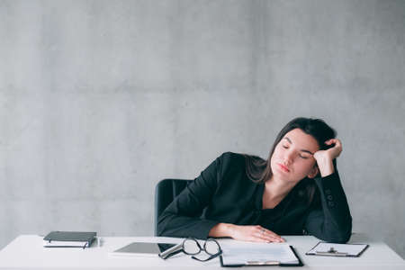 Insomnia and working overtime. Portrait of tired young business woman sleeping at office desk.