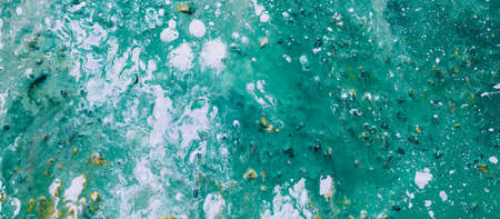 Abstract paint background. White spots randomly covering teal green surface. Fluid liquid rough uneven texture pattern.