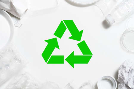 Garbage recycling. Environmental protection. Plastic tableware arranged around green symbol.