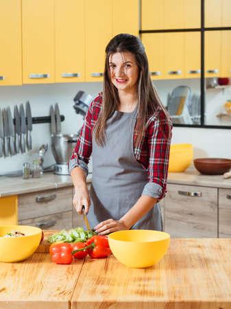 Vegetarische Diät. Gesunder Lebensstil. Junge Dame schneidet Salat, macht Salat mit frischem Gemüse.