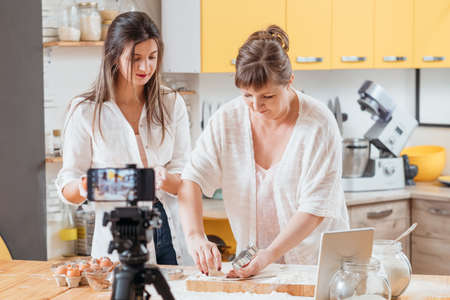 Cooking vlog. Mother daughter cutting dough baking pastry cookies cakes biscuits recording smartphone video tutorial. Banque d'images