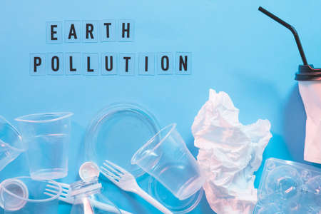 Earth pollution. Plastic littering. Ecology problem. Disposable tableware over blue background. Stock Photo