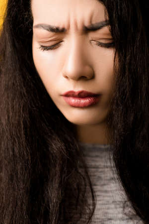 Closeup portrait of upset, regretful emotional brunette girl with disappointed, sorrowful facial expression, eyes closed.