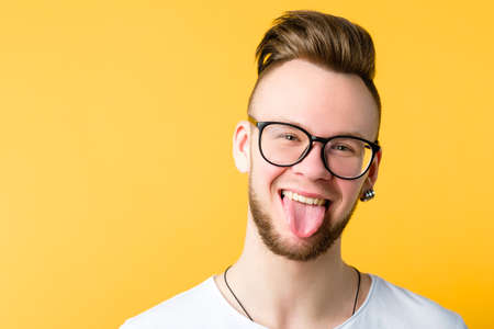 Portrait of positive, cheerful young guy with trendy comb over haircut. Funny emotional man sticking tongue out. Copy space.