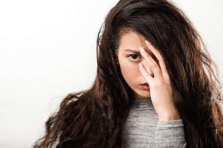 Depression trouble problem. Young woman looking camera. Hand hair covering eye. Intense look fixed gaze. Mental pain.
