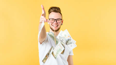 Young man bearded hipster toothy smile throwing dollars at you. Banknotes in air. Banking marketing commerce cashback
