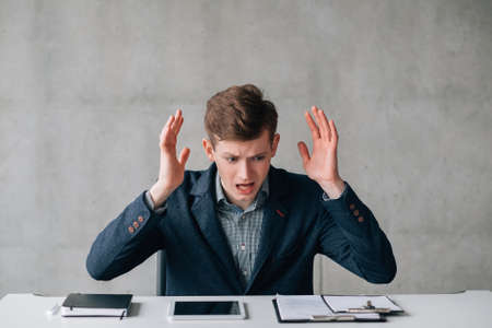 Portrait of young office worker dealing with problems. Guy sitting at desk, raising hands in the air. Scared facial expression. Stockfoto