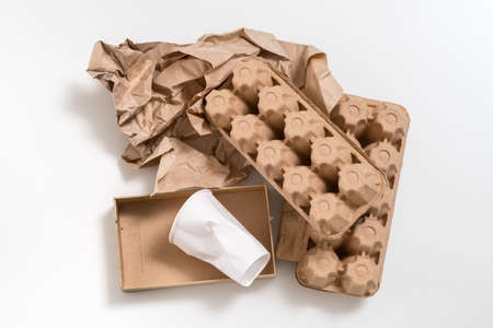 Eco friendly material. Biodegradable waste. Paper boxes and cup arranged on white surface.