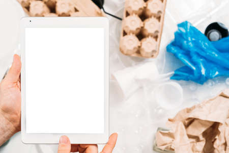 Environmental protection. Social media motivation. Closeup of mockup screen tablet in man hands over garbage littering. Stock Photo