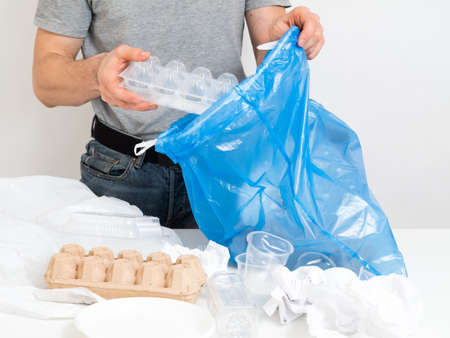 Waste management, sorting, recycling. Man collecting disposable garbage into plastic bag. Stock Photo