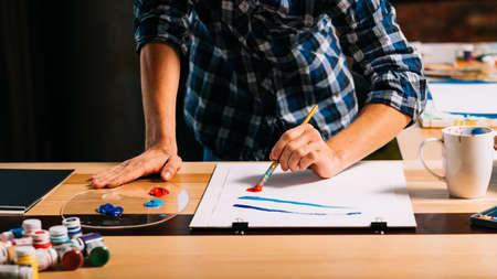 Artist painting. Studio atelier workspace. Sudden inspiration creativity artistry. Man making paint brush strokes on paper. Stock Photo