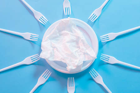 Plastic degradation. Greenhouse gases. Ambient solar radiation. Sun pattern. Disposable forks arranged around plate with tissue.