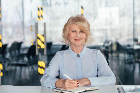 Pleased senior business lady at workplace. Sitting writing in diary planning day. Agenda items objectives achievements. Stock fotó