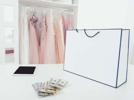 Modern shopping. Luxury boutique. Expensive purchase. Mockup package, bunch of cash and tablet in showroom. 스톡 콘텐츠