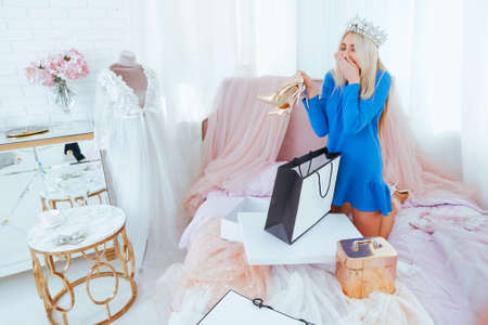 Excited rich girl after shopping in flamboyant bedroom. Blonde lady in tiara on bed unpacking dresses and heeled shoes.