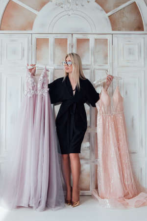 Fashionista lifestyle. Modern showroom. Rich gorgeous lady choosing luxury evening gown for special event.