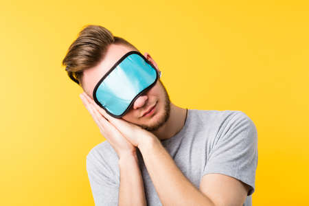 Healthy peaceful sleep rest relaxation. Coziness lifestyle habit. Young man eye mask on. Hands pressed together head tilted.