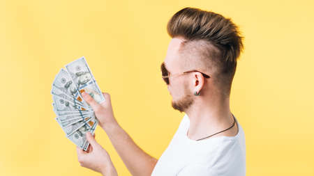 Successful career. Side view portrait of rich hipster guy in sunglasses looking at 100 dollar bill money fan.