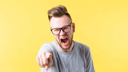 Enraged young man bearded hipster screaming pointing at you. Mouth wide open. Anger irritation bad temper emotion.