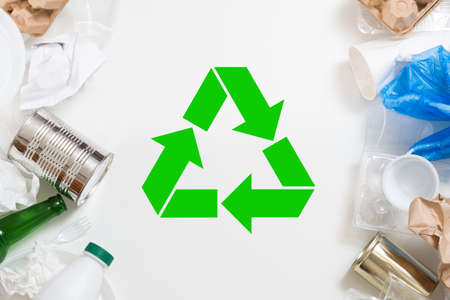Waste sorting and recycling. Plastic, paper, glass, metal garbage arranged over white background. Green symbol in center.