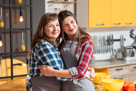 Time together. Family relationships. Smiling mother daughter hugging each other tightly. Cooking leisure hobby relaxation. Stock Photo