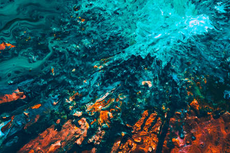 Abstract art texture background. Ocean waves splashing at cliff. Beautiful teal blue and orange paint mixture splotch.