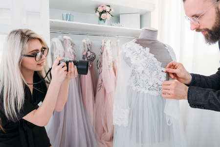 Fashion boutique photoshooting. Creative teamwork. Designer and professional photographer working together in dress showroom.