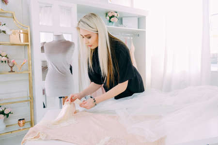 Bespoke service. Modern workshop. Dressmaking business. Lady working on new dress design for customer. Stock Photo