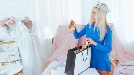 Modern luxury lifestyle. Lady in tiara unpacking new shoes in room with sophisticated interior.