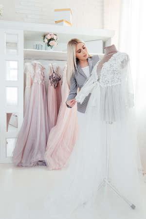 Luksusowy butik. Personal shopper w wykonaniu designerskiej sukni wieczorowej z najnowszej kolekcji. Nowoczesne wnętrze salonu. Zdjęcie Seryjne