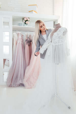 Luxury boutique. Personal shopper performing designer evening gown from latest collection. Modern showroom interior. Stockfoto