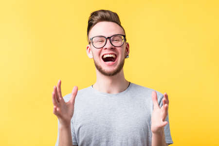 Happiness excitement elation. Thrilled young man describing gesturing. Extreme positive emotion feeling facial expression. Stockfoto