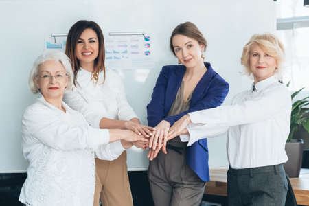 Business women hands together. Equality unity. Cooperation collaboration teamwork. Diversity strength success power. Stock Photo