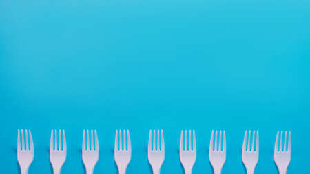 Air pollution. Plastic littering. Ecology problem. White disposable fork row at bottom of sky blue background. Copy space.