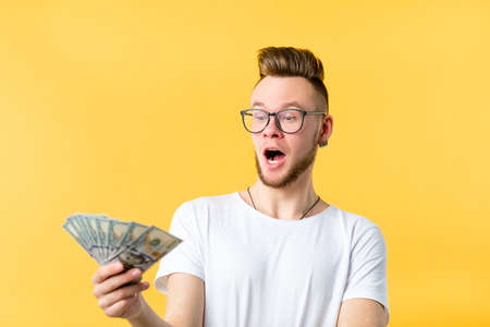 Young man bearded hipster holding dollar bills cash looking surprised open mouth. Generous sum payment reward refund