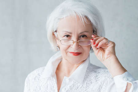 Senior lady portrait. Confident elderly female looking intently over glasses. Curious evaluative self assured business woman.