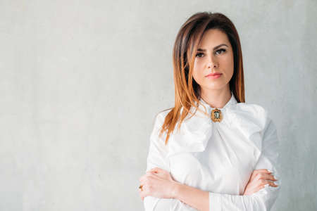 Young woman portrait. Serious facial expression. Confident business female arms folded. Classy smart corporate ceo boss Stok Fotoğraf